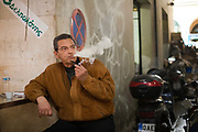 A man lights and smokes a pipe outside a small cafe in the  Athens Central Market on Athinas Street. Athens, Greece