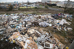 © Licensed to London News Pictures. 29/03/2018. London, UK. A large pile of waste and rubbish has been dumped in an area of scrap land next to houses and a recreation park in Edmonton, in Enfield, north London. Local residents are calling it a 'river of rubbish' and say it has been there for a month and are campaigning for it's removal.  Photo credit: Peter Macdiarmid/LNP