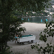 """a child try to play pool table on Perast beach. There are several arguments about the derivation of the name  """"Montenegro"""", one of these relates to dark and deep forests  that once covered the Dinaric Alps, as it was possible to see them from the sea. <br /> Mostly mountainous with 672180 habitants on an area of 13812 Km², with a population density of  48 habitants/Km². <br /> It borders with Bosnia, Serbia, Croatia, Kosovo and Albania but  Montenegro has always been alien to the bloody political events that characterized Eastern Europe in recent decades. <br /> From 3 June 2006, breaking away from Serbia, Montenegro became an independent state. <br /> In the balance between economy devoted to sheep farming and a shy tourist, mostly coming from Bosnia and Herzegovina, Montenegro looks to Europe with a largely unspoiled natural beauty. <br /> Several cities in Montenegro, as well as the park Durmitor, considered World Heritage by UNESCO but not yet officially because Montenegro has yet to ratify the World Heritage Convention of UNESCO."""