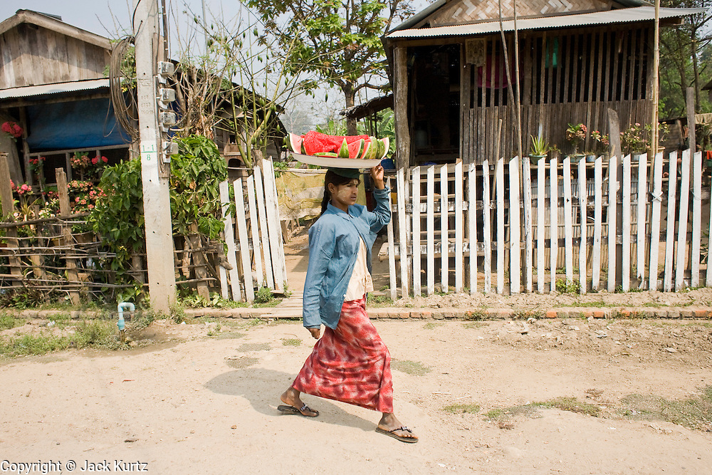 26 FEBRUARY 2008 -- MYAWADDY, MYANMAR: A water melon vendor walks through Myawaddy, Myanmar. Myawaddy, a town of about 65,000, is just across the Moei River from Mae Sot, Thailand and is one of Myanmar's leading land ports for goods going to and coming from Thailand. Most of the businesses in the town are geared towards trade, both legal and illegal, with Thailand. Human rights activists from Myanmar maintain that the Burmese government controls the drug smuggling trade between the two countries and that most illegal drugs made in Myanmar are shipped into Thailand from Myawaddy.   Photo by Jack Kurtz