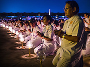 "22 FEBRUARY 2016 - KHLONG LUANG, PATHUM THANI, THAILAND:  People pray and meditate on the plaza in front of the chedi during Makha Bucha Day services at Wat Phra Dhammakaya.  Makha Bucha Day is a public holiday in Cambodia, Laos, Myanmar and Thailand. Many people go to the temple to perform merit-making activities on Makha Bucha Day, which marks four important events in Buddhism: 1,250 disciples came to see the Buddha without being summoned, all of them were Arhantas, Enlightened Ones, and all were ordained by the Buddha himself. The Buddha gave those Arhantas the principles of Buddhism, called ""The ovadhapatimokha"". Those principles are:  1) To cease from all evil, 2) To do what is good, 3) To cleanse one's mind. The Buddha delivered an important sermon on that day which laid down the principles of the Buddhist teachings. In Thailand, this teaching has been dubbed the ""Heart of Buddhism."" Wat Phra Dhammakaya is the center of the Dhammakaya Movement, a Buddhist sect founded in the 1970s and led by Phra Dhammachayo.     PHOTO BY JACK KURTZ"