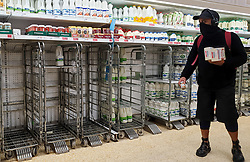 © Licensed to London News Pictures. 21/09/2021. London, UK. A shopper wearing a face covering walks past empty shelves of fresh milk, just after 8am this morning in Sainsbury's, north London, Fears of food shortages grow after two of the UK's biggest Carbon Dioxide (CO2) producers halted production last week due to soaring gas prices. UK food producers and supermarkets are warning that shoppers are likely to face food shortage caused by a lack of gas could hit this week. Photo credit: Dinendra Haria/LNP