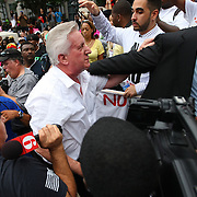 """A George Zimmerman supporter (white shirt) is escorted out of the crowd during the No Justice No Peace- """"March Against Gun Violence""""  walk from Lake Eola in downtown Orlando, to the Orange County Courthouse on Wednesday, July 17, 2013. The man was walking around with a sign that said Zimmerman was not guilty. (AP Photo/Alex Menendez)"""