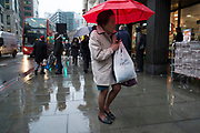 People out and about in the rain in the City of London, England, UK. January in the UK sees wet and cold weather, almost like a dreary scene from days gone by.