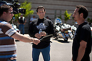 Candidate for New Mexico Lt-Governor Joseph Campos watches from the background as his brother Santiago gives a television interview prior to the start of a motorcycle Benefit Ride for UNM Children's Hospital from Albuquerque to Madrid New Mexico on May 16th 2010.