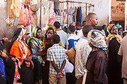 Local people gather to buy meat and fish at the main market in Stone Town on 6th December 2008 in Zanzibar, Tanzania. The searing heat and humidity and the exposed meat makes for an incredible atmosphere as market traders and customers alike barter for the produce. Zanzibar is a small island just off the coast of the Tanzanian mainland in the Indian Ocean. In part due to its name, Zanzibar is a travel destination of mystical reputation, known for its incredible sealife on its many reefs, the powder white coral sand beaches and the traditional cultivation of spices.