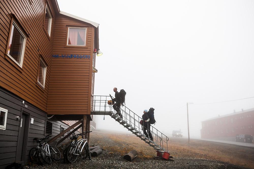 Dariusz Ignatiuk (left) and Agnienka Piechota, Polish geologists from the University of Silesia, check into a hotel in Longyearbyen, Svalbard,  on the last night of their Arctic field season.