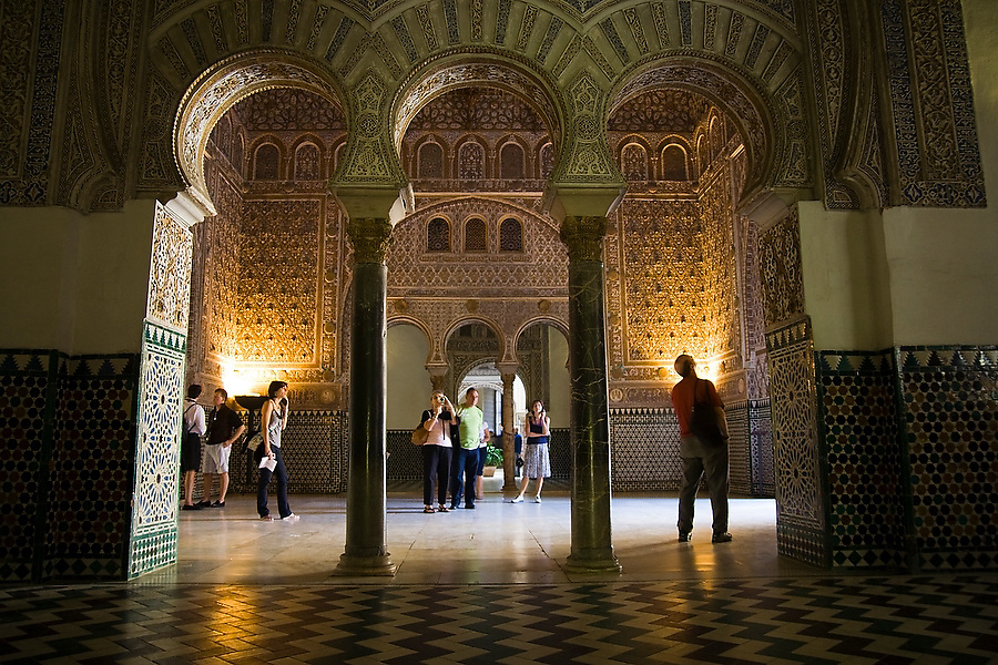 Tourists stand in a large hall inside the Alcazar, Sevilla, Andalusia, Spain.