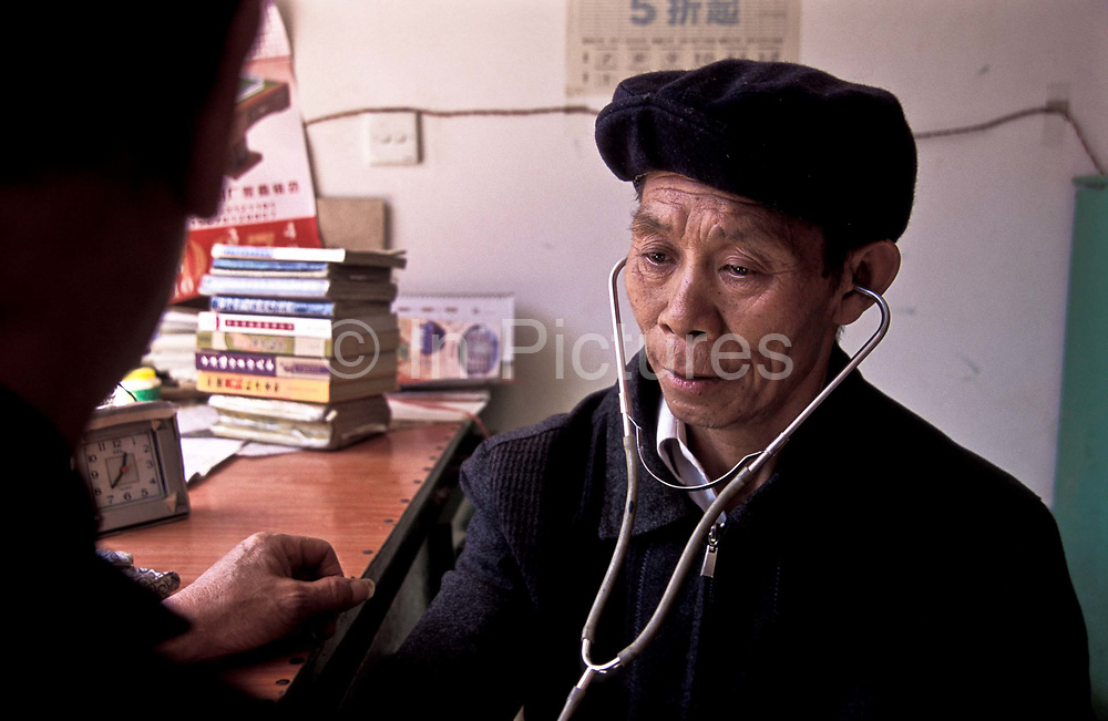 Chen Yi He, Chinese Herbalist, attends to patients in his herbal acupuncure and cupping, (traditional Chinese medicine ) clinic in Xiao Meng Yang town, Yunnan, province, China
