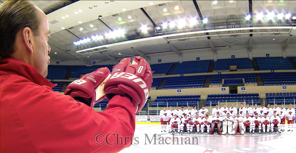 Head Hockey Coach Mike Kemp arranges his team on media as they prepare for the team photo.<br /> photo by chris