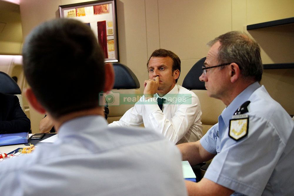 France's President Emmanuel Macron, 2nd right, confers with officials aboard the presidential plane en route to Guadeloupe Island, the first step of his visit to French Caribbean islands, Tuesday, Sept. 12, 2017. Seated at the table are director of the rescue service (Securite Civile), Jacques Witkowski, back to camera, and Director General of the Gendarmerie Nationale, Richard Lizurey, right. Photo by Christophe Ena/Pool/ABACAPRESS.COM