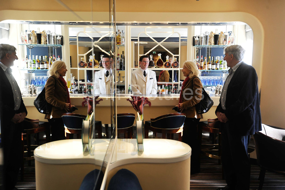 """A barman speaks to visitors in the American bar at the Savoy Hotel in London. The iconic hotel reopened after a three year refit that cost £220 million ($350 million). The Savoy Hotel is a located on the Strand, in central London. Built by impresario Richard D'Oyly Carte the hotel opened on 6 August 1889. It was the first in the Savoy group of hotels and restaurants owned by Carte's family for over a century. It has been called """"London's most famous hotel"""" and remains one of London's most prestigious and opulent hotels, with 268 rooms and panoramic views of London."""