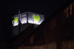 London, UK. 14th February, 2019. A message 'Grenfell Forever In Our Hearts' appears at the top of Grenfell Tower on the evening of the Grenfell Silent Walk. Members of the Grenfell community and firefighters take part in the Grenfell Silent Walk around North Kensington on the monthly anniversary of the fire on 14th June 2017. 72 people died in the Grenfell Tower fire and over 70 were injured.