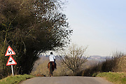 Lone girl rides horse in country village lane, Bourton-on-the Waer, The Cotswolds, England,  United Kingdom