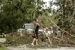A barefoot Dan Rodgers, left, and his brother Keith, right, help clear a tree out of the middle of Villanova Road in Kissimmee, Fla. on Monday, September 11, 2017. The brothers live nearby in Kissimmee and stopped by this neighborhood to check on their father after Hurricane Irma plowed through Florida. Photo by Orlando Sentinel/TNS/ABACAPRESS.COM