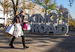 © Licensed to London News Pictures. 04/11/2020. London, UK. A shopper walks past a huge King's Road sign in Chelsea. Last minute shopping on the King's Road in Chelsea, London with only a few hours left before another National lockdown begins. Prime Minister Boris Johnson announced last Saturday a new Covid-19 lockdown restrictions for England from Thursday (tomorrow) with pubs, restaurants, non-essential shops and gyms to close. The Prime Minister also warned MPs that deaths from Covid-19's second wave could be twice as high as the first ahead of MPs voting on the Government's 4 week lockdown measures today. Photo credit: Alex Lentati/LNP