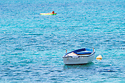 A white and blue rowing boat moored by a white buoy on a bright blue sea. A person floating on an inflatable air mattress. Uvala Sumartin bay between Babin Kuk and Lapad peninsulas. Dubrovnik, new city. Dalmatian Coast, Croatia, Europe.