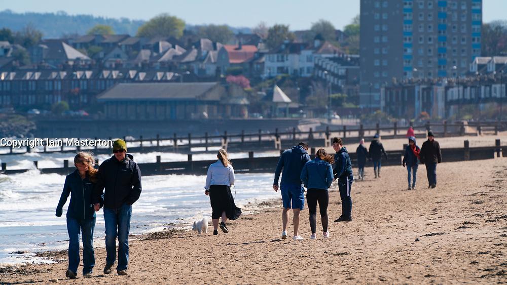 Portobello beach and promenade near Edinburgh during Coronavirus lockdown on 19 April 2020. People walking on beach.