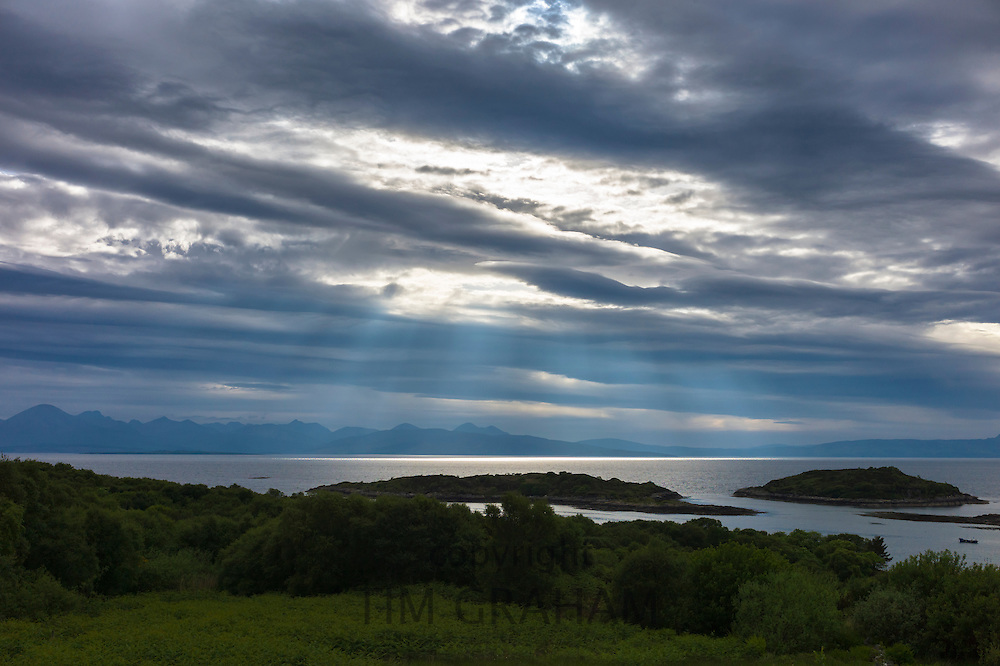 Sun rays break through cloud in skyscene with view of Isle of Skye and Cuillin mountains from Kyle of Lochalsh on North West Coast of Scotland