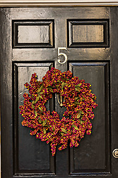 December 21, 2017 - Charleston, South Carolina, United States of America - A black wooden door of a historic home decorated with a Popcorn Berry Christmas wreath on Tradd Street in Charleston, SC. (Credit Image: © Richard Ellis via ZUMA Wire)