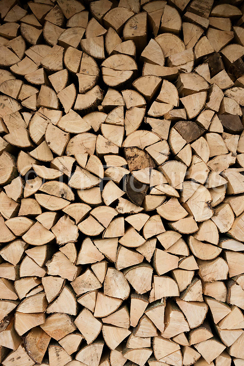 Piles of sawn logs, ready for a winter home fire, stays dry under cover in a small holding shed. The ends of this timber is kept out of the weather, drying in readiness for the family hearth that heats the home. Originally tree trunks from nearby woodland, it has been chopped into quarters and sawn so its flat ends neatly fit into a tidy pile.