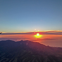 The sun sets over Great Salt Lake, Salt Lake City and the Wasatch Mountains in Utah.
