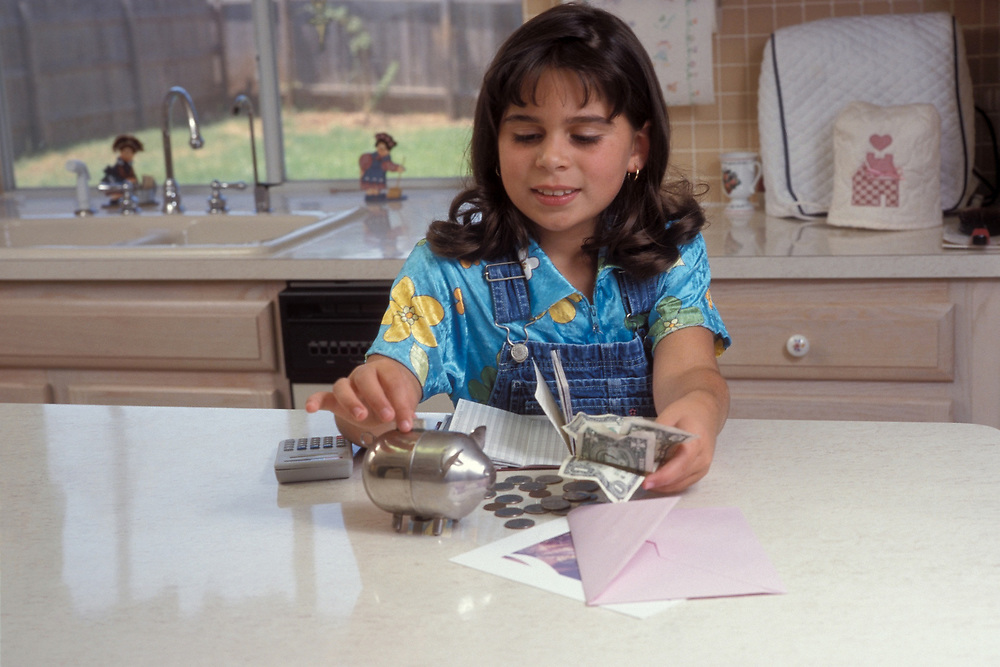 8 year old Panamanian American girl puts coins into piggy bank after counting them.<br /> ©Bob Daemmrich/
