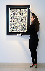 © Licensed to London News Pictures 10/04/2013.A Christie's employee straightens the Jackson Pollock painting ' Number 19', estimated between $25 - $35 million, that is on display at Christie's in central London and due to go on auction for the first time in 20 years, on the 15th May in New York. .London, UK.Photo credit: Anna Branthwaite
