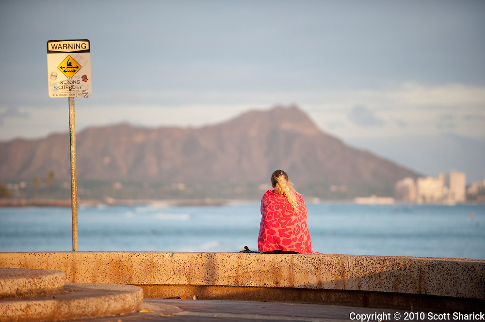 A woman with a red towel sits on the ledge at Point Panic next to a warning sign.