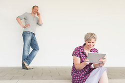 Mature woman using digital tablet while mature man talking on cell phone, smiling