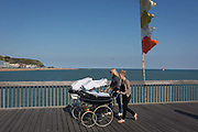 Two mothers push their classic design prams on Hastings Pier, on 29th April 2017, at Hastings, East Sussex, England.