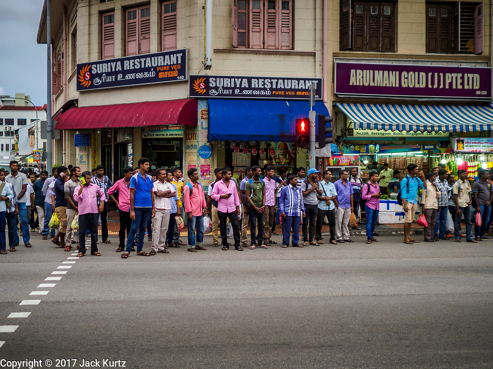 """09 JULY 2017 - SINGAPORE: Guest workers from the Indian sub-continent line Serangoon Road in the heart of Singapore's """"Little India"""" neighborhood. There are hundreds of thousands of guest workers from the Indian sub-continent in Singapore. Most work 5 ½ to six days per week. On Sundays, the normal day off, they come into Singapore's """"Little India"""" neighborhood to eat, drink, send money home, go to doctors and dentists and socialize. Most of the workers live in dormitory style housing far from central Singapore and Sunday is the only day they have away from their job sites. Most work in blue collar fields, like construction or as laborers.    PHOTO BY JACK KURTZ"""