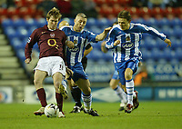 Photo: Aidan Ellis.<br /> Wigan Athletic v Arsenal. Carling Cup. Semi Final, 1st Leg.<br /> 10/01/2006.<br /> Arsenal's Alexander Hleb hols off Wigan's Graham Kavanagh and Jimmy Bullard