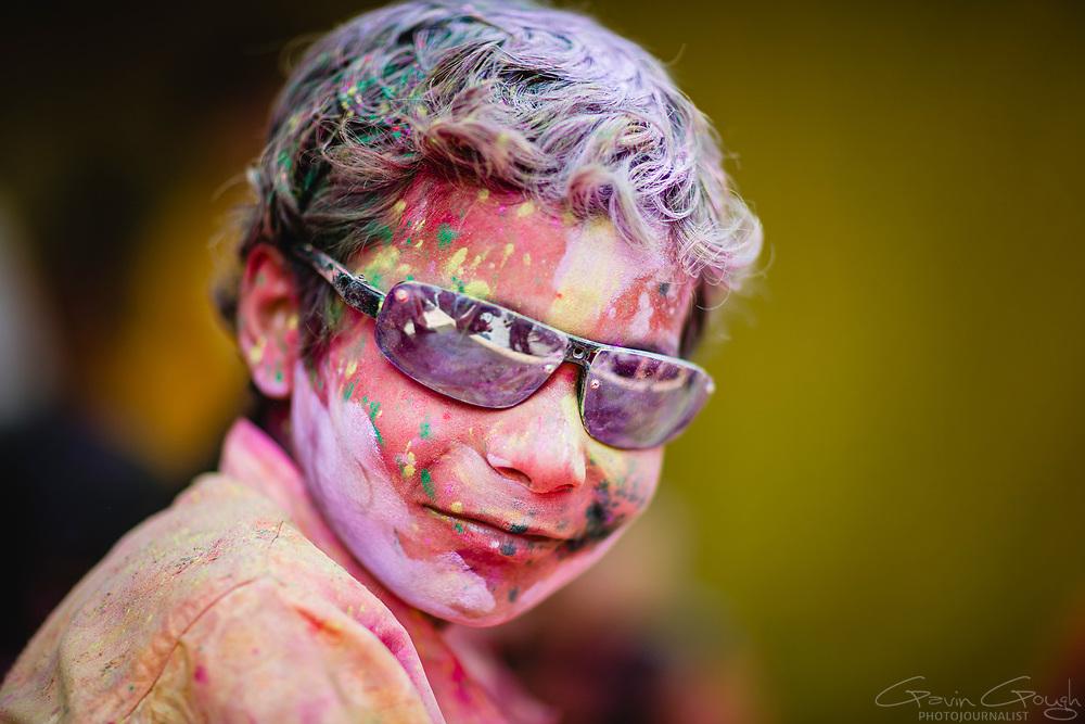 A boy covered in coloured powder during celebrations for the Hindu Holi festival, Nanda Bhavan or Nandagram Temple, Nandgaon, India