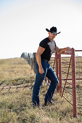 hot rugged cowboy outdoors on a ranch by a fence