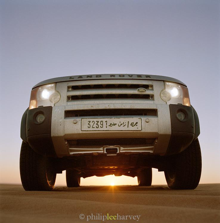 Sun setting behind a Landrover Discovery 4x4, Sahara Desert, Libya
