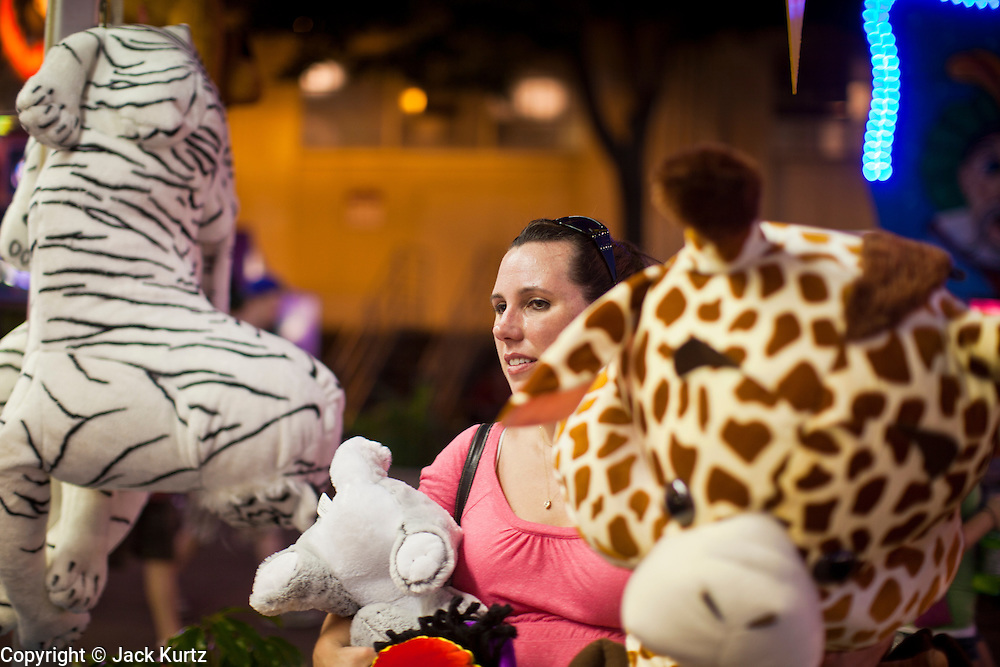 """01 SEPTEMBER 2011 - ST. PAUL, MN:  A woman with a stuffed animal on the midway at the Minnesota State Fair. The Minnesota State Fair is one of the largest state fairs in the United States. It's called """"the Great Minnesota Get Together"""" and includes numerous agricultural exhibits, a vast midway with rides and games, horse shows and rodeos. Nearly two million people a year visit the fair, which is located in St. Paul.  PHOTO BY JACK KURTZ"""