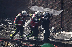 © Licensed to London News Pictures. 14/06/2017. London, UK. Police officers with riot shields escort Firemen underneath shields to protect themselves from falling debris as they enter the tower block. The scene of a huge fire at Grenfell tower block in White City, London. The blaze engulfed the 27-storey building with 200 firefighters attending the scene. There were reports of people trapped in the building. Photo credit: Ben Cawthra/LNP