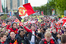 © Licensed to London News Pictures . 13/05/2013 . Manchester , UK . 1000s of fans move up Sir Matt Busby Way following the bus . Manchester United trophy parade on Sir Matt Busby Way , from Old Trafford to Manchester City Centre this evening (Monday 13th May) . The team are celebrating their 20th league title win and commemorating the retirement of manager , Sir Alex Ferguson , by carrying the trophy on an opened top bus through the city . Photo credit : Joel Goodman/LNP