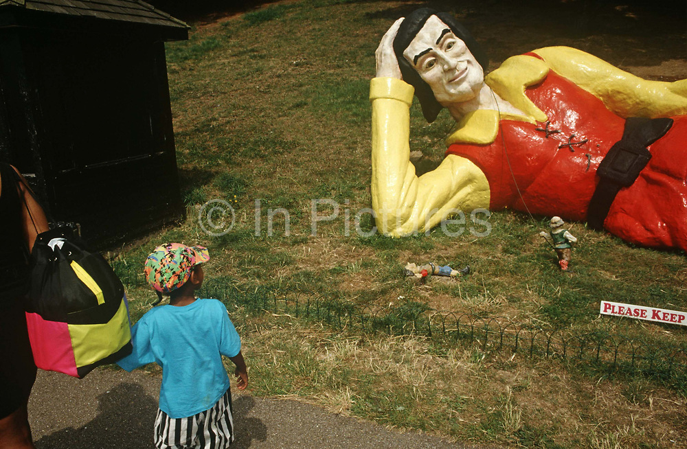 """A young boy looks at a reclining giant fibreglass figure resembling Gulliver's Travels on Southend-on-Sea seafront. As if in the fantasy world of Lilliput (the novel by Johnathan Swift), the larger-than-life figure lies on summer grass for families to walk past. Smaller, people models can be seen at the giant's elbow, one of which has fallen over. And the words """"Please Keep .. (off the grass)"""" are on a sign deterring kids from jumping over and climbing on the man."""