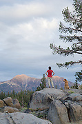 Woman and dog (golden retreiver) watching alpenglow on Highland Peak, Toiyabe National Forest, California