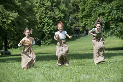 Three girls jumping in sack race in a field, Munich, Bavaria, Germany