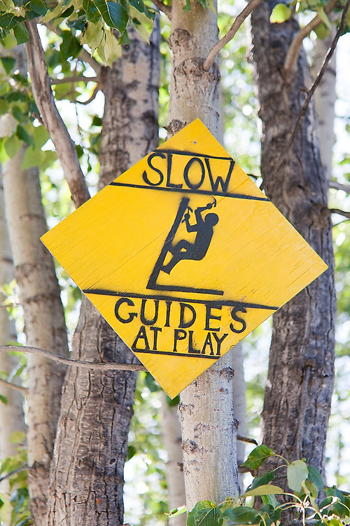 """A sign reads """"SLOW Guides at Play"""" outside the entrance to the St. Elias Alpine Guides headquarters in McCarthy, Alaska."""