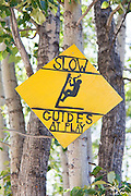 "A sign reads ""SLOW Guides at Play"" outside the entrance to the St. Elias Alpine Guides headquarters in McCarthy, Alaska."
