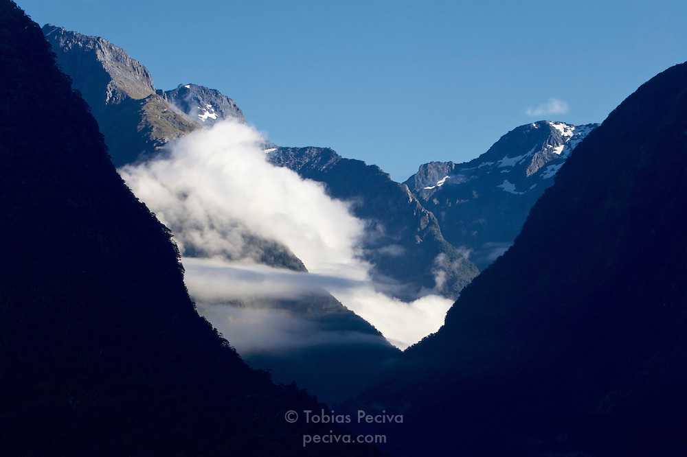 Early morning clouds wrap around mountains in Milford Sound, Fiordland, New Zealand.