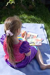 Little girl reading a book in the garden,