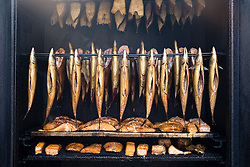 View of fish being smoked in mobile smokehouse at outdoor organic farmers market in Prenzlauer Berg in Berlin , Germany