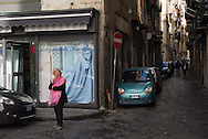 A woman wears a red scarf in front of a building advertising a blue dress in Naples, Italy