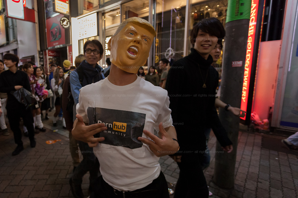 A man in a Donald Trump mask and Porn-Hub T-shirt during the Halloween celebrations Shibuya, Tokyo, Japan. Saturday October 27th 2018. The celebrations marking this event have grown in popularity in Japan recently. Enjoyed mostly by young adults who like to dress up, drink , dance and misbehave in parts of Tokyo like Shibuya and Roppongi. There has been a push back from Japanese society and the police to try to limit the bad behaviour.