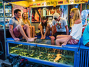 """03 JUNE 2016 - SIEM REAP, CAMBODIA: Tourists experience a """"Fish Massage"""" at a street side massage parlor near Pub Street in Siem Reap, Cambodia. Pub Street is the center of Siem Reap's dining and nightlife.     PHOTO BY JACK KURTZ"""